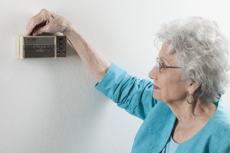 Older woman adjusting the thermostat in her Utica, Kentucky home.