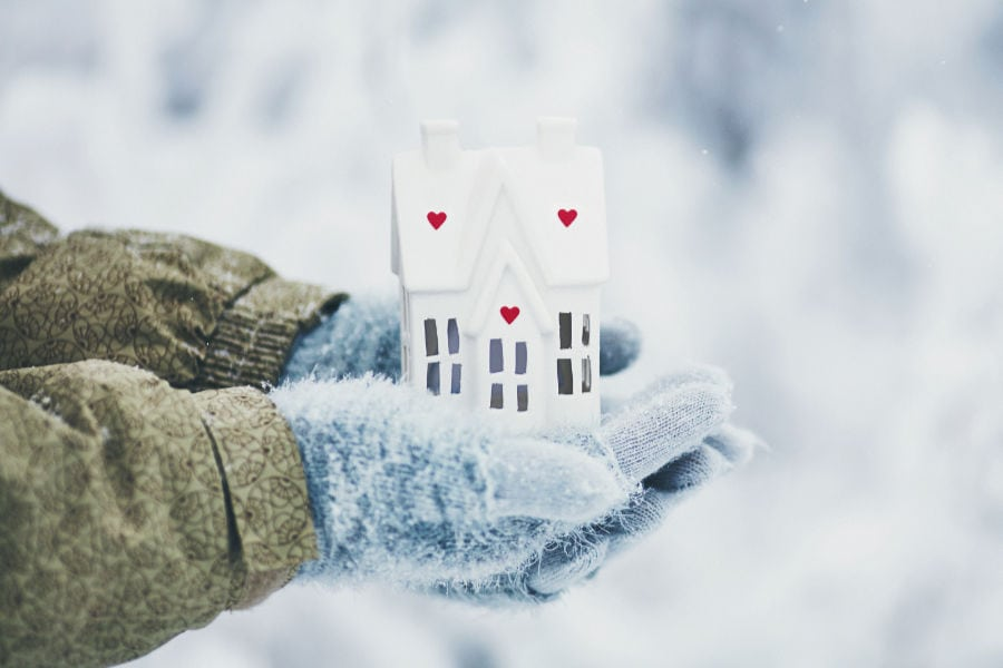 Gloved hands holding a small white bird house in Philpot, Kentucky.