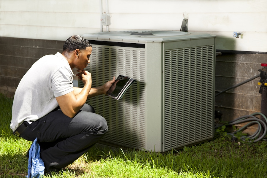 HVAC technician inspecting an air conditioning unit outside in Owensboro, KY.