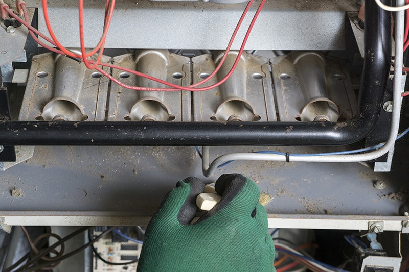 A gloved hand repairing the inside of an appliance | 5 Reasons to Schedule a Fall Furnace Clean and Check | Philpot, KY